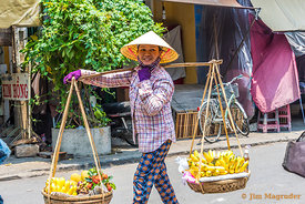 A Vietnamese Woman Carries Baskets In Hoi An