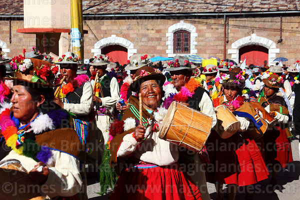 Woman beating bombo drum with yapuchiris dance group from Acora village, Virgen de la Candelaria festival, Puno, Peru