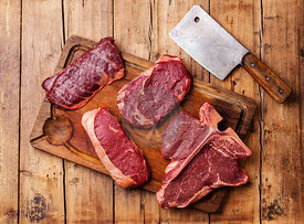 Different types of Raw fresh meat Steaks and meat cleaver on cutting board on wooden background