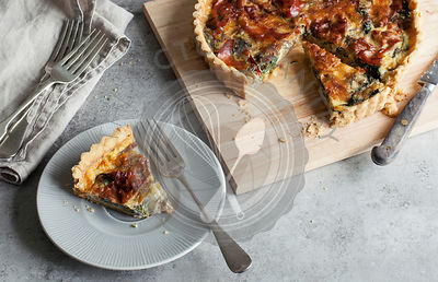 Proscuitto and Swiss Chard Tart on wooden chopping board