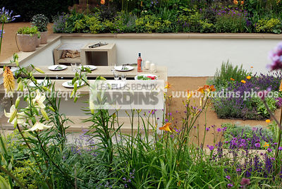 Jardin contemporain en contre-bas. Meuble de jardin : table et banc. Terrasse. Designer : Thomas Hoblyn Design Agency. Hampton Court. Angleterre