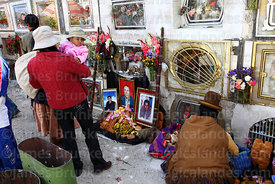 Aymara woman sitting next to tomb of deceased relative with bread offerings in cemetery, Todos Santos festival, La Paz, Bolivia