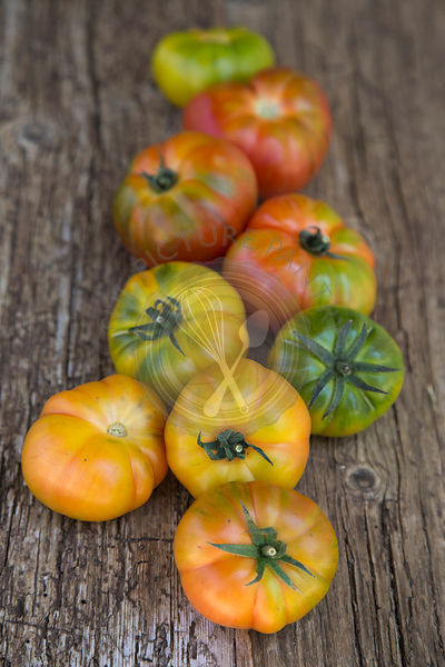 cascading group of Spanish grown Raf striped tomatoes on wooden rustic board