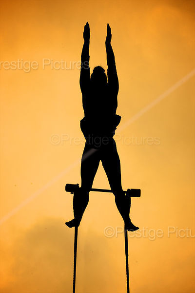 Silhouette of Aerial Performer Swinging against a Yellow Sky