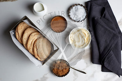 Snickerdoodle cookies with ingredients in vintage tins on a white marble table and black linen