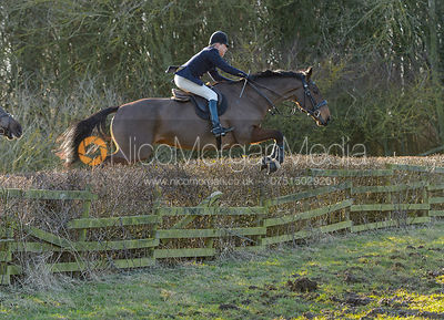 Nicky Hanbury jumping a hedge at Town Park Farm - The Cottesmore at Town Park Farm