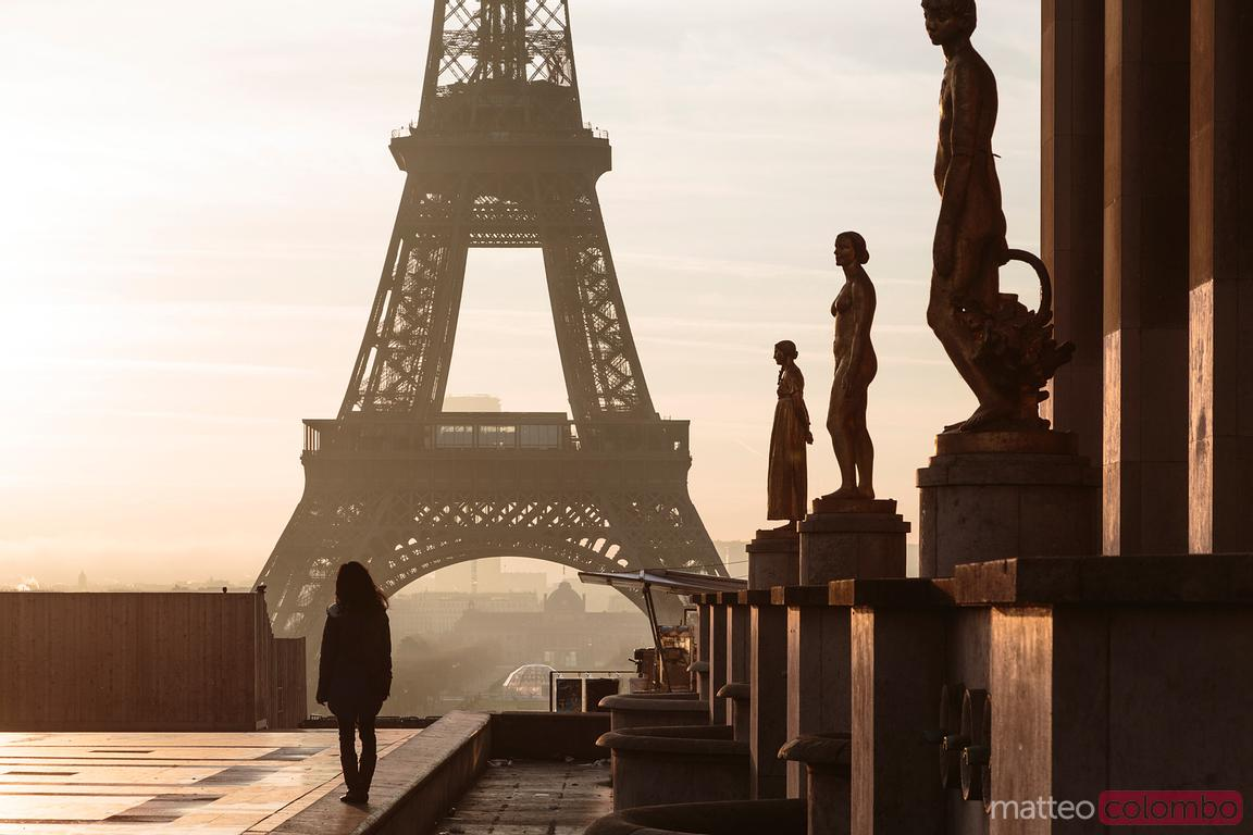 Woman standing in front of the Eiffel tower, Paris