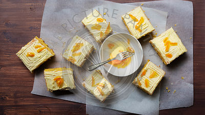 Pieces of orange and poppy seed cake with a bowl of candied peel.