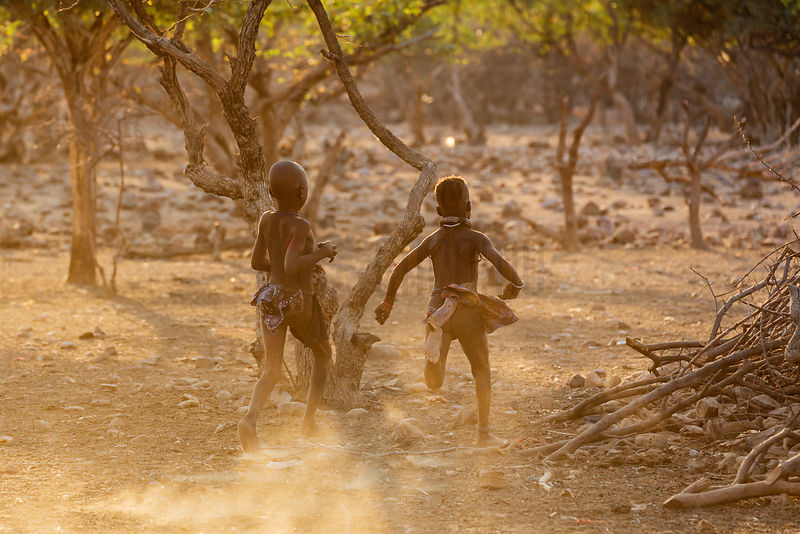 Himba Children Running in Village at Sunrise