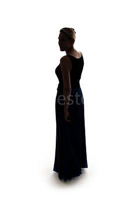 A silhouette of a woman in a long dress looking over her shoulder – shot from eye level.