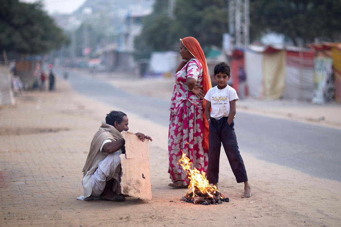 A family warms by a fire on a cold winter morning in Pushkar, Rajasthan, India