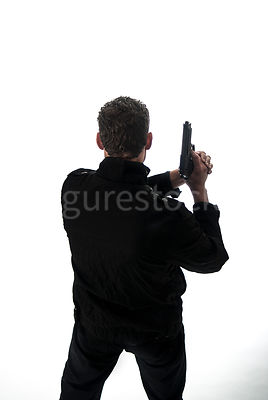 A mystery man in a black jacket holding a gun and looking down from a rooftop.