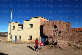 Children walking past adobe chulpa and house in Curahuara de Carangas, Oruro Department, Bolivia