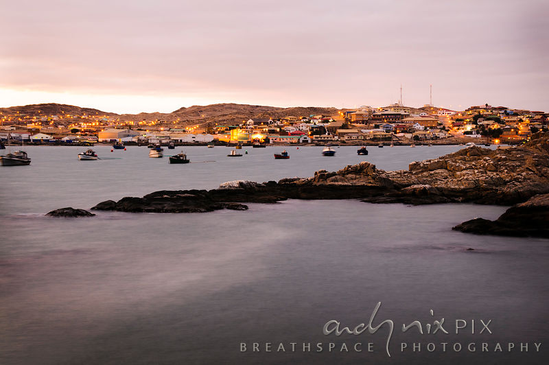 A view of a harbour in a desert town at dawn, lights shining on the streets, sea in the foreground blurred