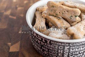dog bowl with dog biscuits on wood background