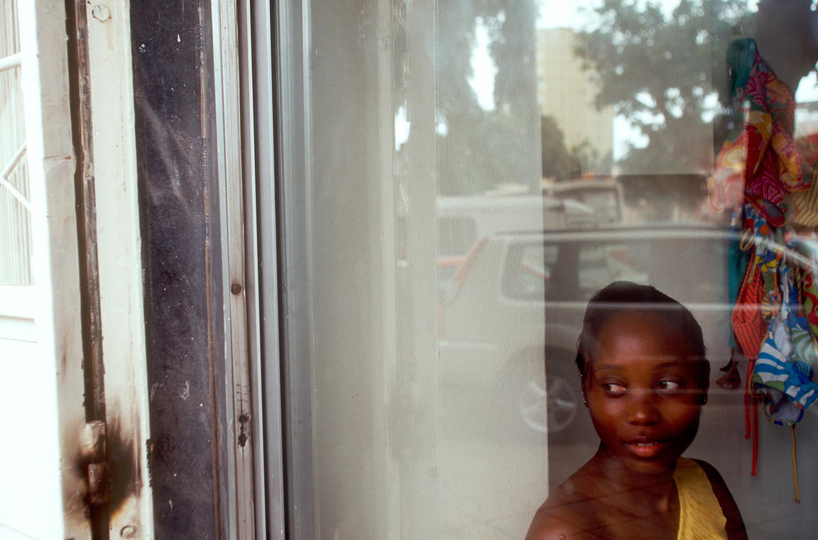 Angola - Luanda - A shop girl watches the expensive cars driving the streets of Luanda