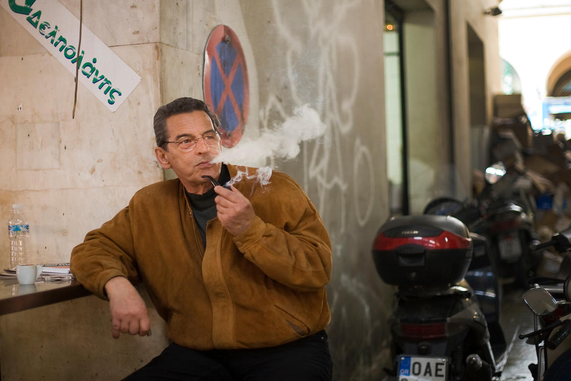 Greece - Athens - A man lights and smokes a pipe outside a small cafe in the  Athens Central Market