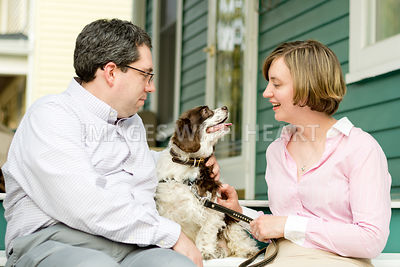 Dog with man and woman interacting on porch