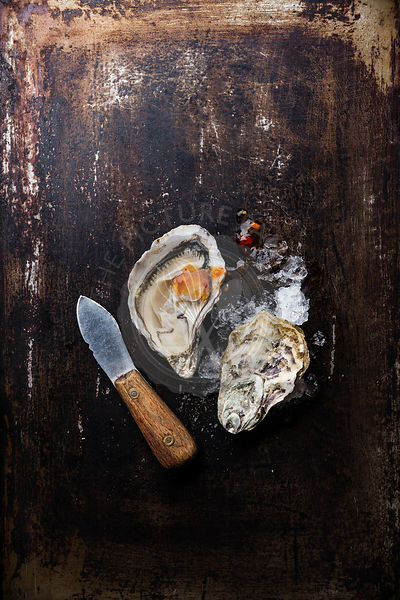 Oyster and oyster knife on dark metal background with ice and spicy sauce