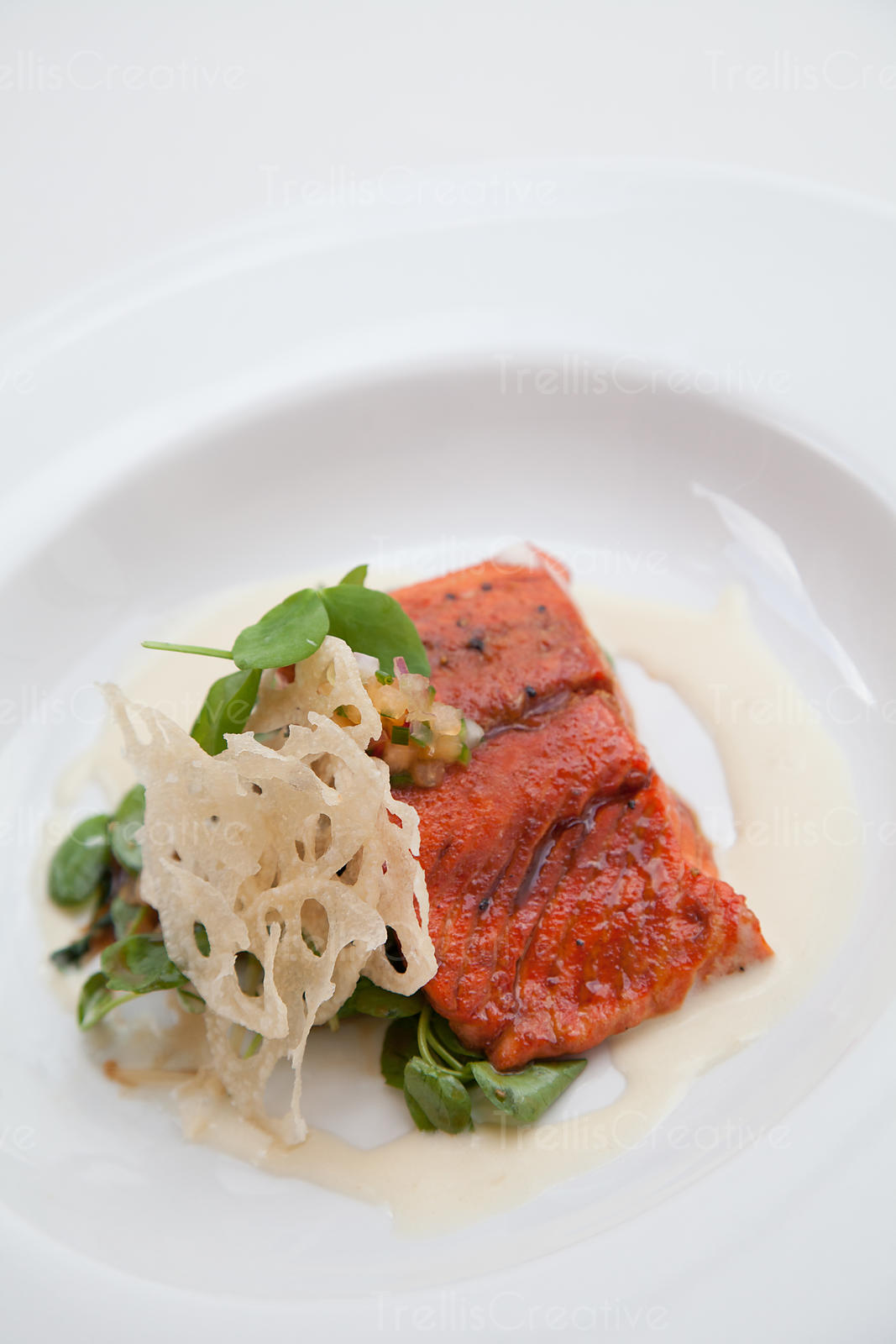 Close-up of a grilled salmon steak on a white plate with lotus root garnish