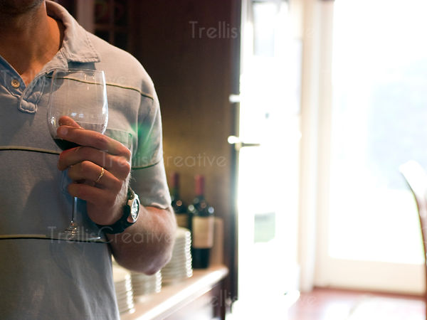 A young man holds a glass of red wine at a party