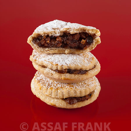 Stacked mince pies on red background