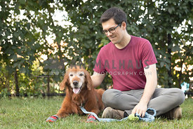 man sitting in park with senior retriever dog