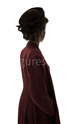 A semi-silhouette of a 1940's woman in a red coat and hat, looking away – shot from eye-level.