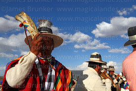 Local leader wearing a poncho playing horn or pututu, Orinoca, Bolivia