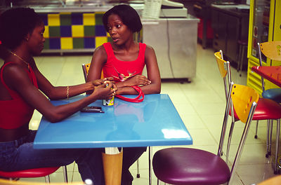 Angola - Luanda - Two middle class girls sit in a diner