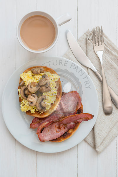 Egg, bacon and mushroom bagel, with a cup of tea.