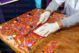 Detail of woman cutting up turrón during Señor de los Milagros festival, Lima, Peru