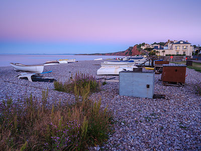 A lilac twilight with boats on the pebbled beach at Budliegh Salterton, Devon, UK