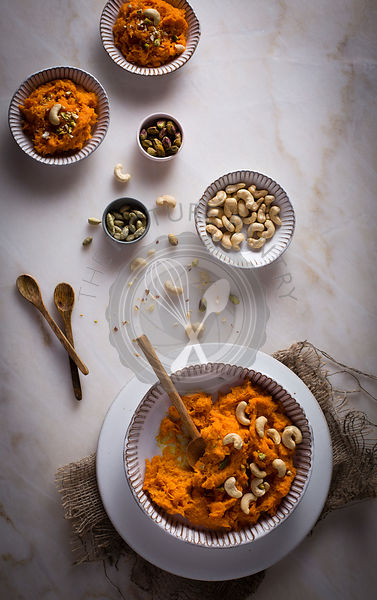 Carrot Halwa / Carrot pudding with nuts in a ceramic bowl on top view on a marble table