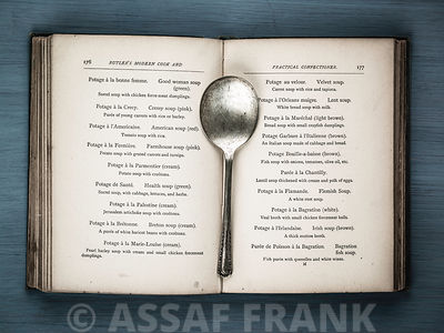 Old cookery book open with an old spoon