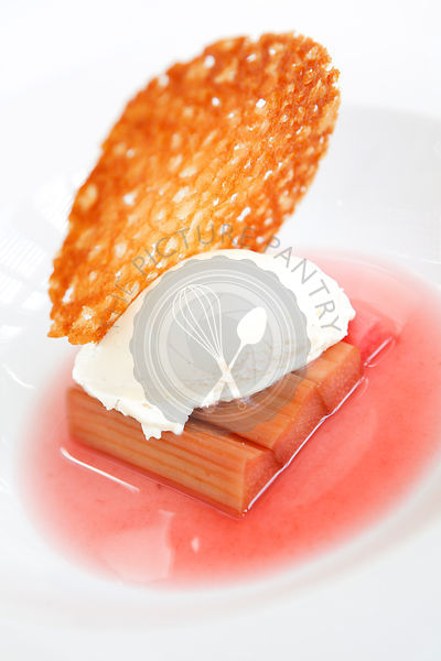 Dessert of spiced rhubarb with cream and a brandy snap biscuit.