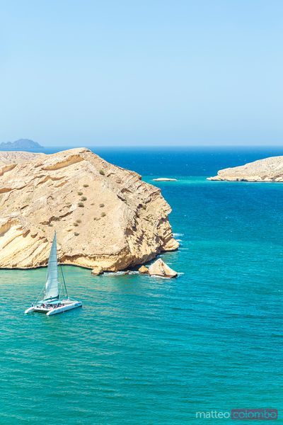 Oman, Muscat, Qantab. Rocky coastline with catamaran sailing