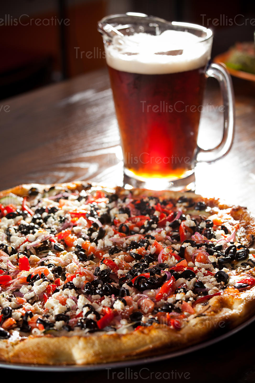 A pitcher of beer and a delicious hot pizza pie in a pizzeria