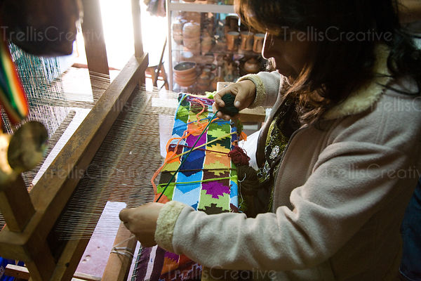 Local craftwoman works an old style loom to make woven tapestries