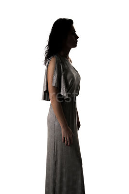 A semi-silhouette of a woman in a grey dress– shot from eye level.