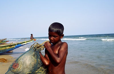 Child carrying fish, Puri beach, India