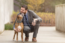 boxer dog kissing man in suit