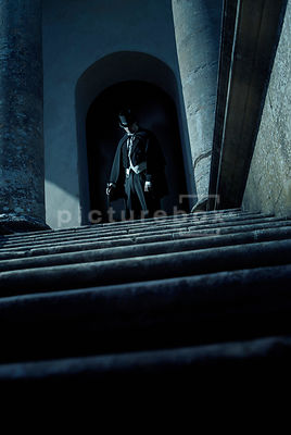 An atmospheric image of a Victorian man lurking in the shadows at the top of some steps, looking out from an old church.