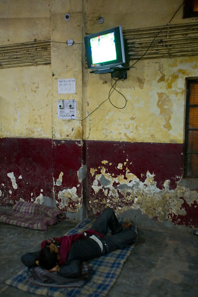India - Delhi - Homeless men watch television in the Fatepuri night shelter