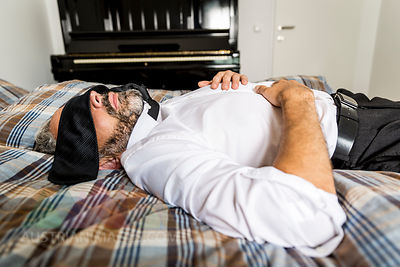 Businessman lying on his bed with tie covering his eyes