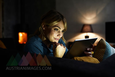 Portrait of smiling woman using tablet on the couch at home in the evening