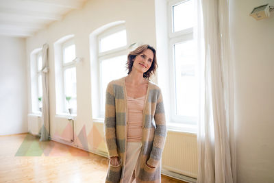Portrait of smiling mature woman standing in empty room