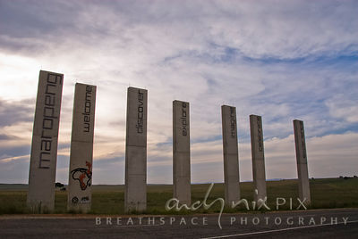 Monoliths marking the entrance to the Cradle of Humankind vistitor center (Maropeng), setting sun behind in a cloudy blue sky