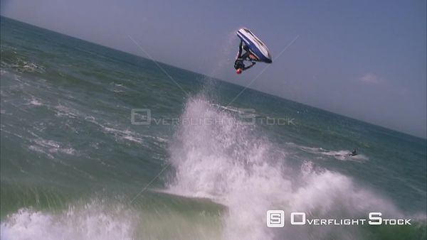 Aerial of a jetskier ramping a wave, flipping head over heels in the air and landing. KwaZulu Natal South Africa