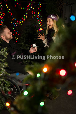 Man in a wheelchair proposing to his girlfriend in front of a Christmas Tree